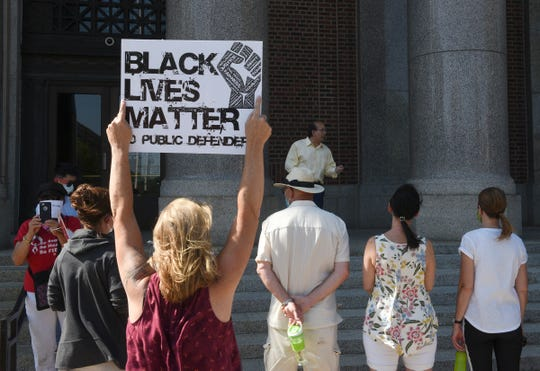 A Black Lives Matter sign is held up on the steps of the Stearns County Courthouse Monday, June 8, 2020, in St. Cloud.