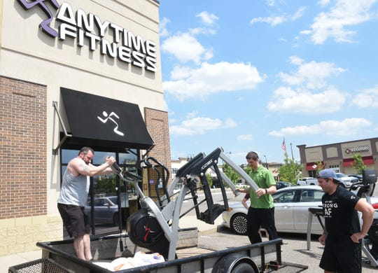 Gary Ronning and Jake Lubbesmeier move exercise equipment in front of Anytime Fitness Monday, June 8, 2020, in Sauk Rapids. Co-owner John Schultz (far right) said the gym is selling nine machines to meet new safety measures.