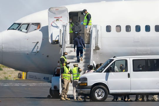 """Children board a flight as they are expelled from the United States on April 19, 2020 at the El Paso International Airport. Granted new authority by the CDC amid the COVID-19 pandemic, border agents have expelled 2,175 """"single minors"""" to their home countries."""
