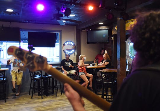 Socially distant music fans in masks watch the return of Lower Case Blues to The Pond in Rehoboth Beach over the weekend. With restaurants now open at 30 percent capacity, a few venues have also brought back live music.