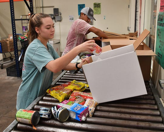 Volunteers Gracie Dunn and Brandon Ramirez fill boxes with non-perishable foods at the Wichita Falls Area Food Bank.