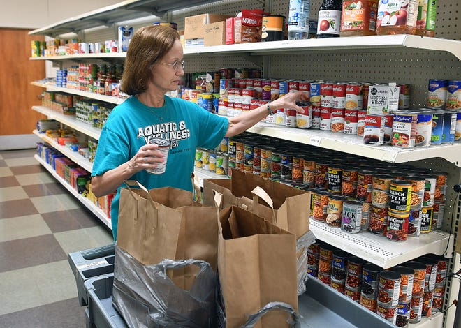 In this file photo, Mary Gwin, volunteer pantry coordinator, sacks up foods for client meals from the pantry at Interfaith Outreach Services.