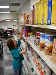 Pantry Coordinator Mary Gwin organizes foods in the pantry of Interfaith Outreach Services in this file photo.