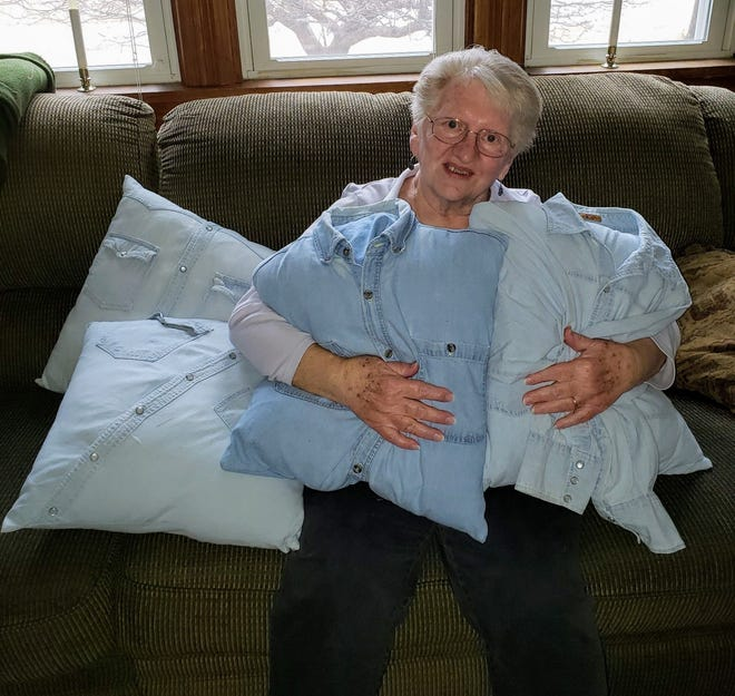 Susan holds some of the pillows made from Bob's work shirts.