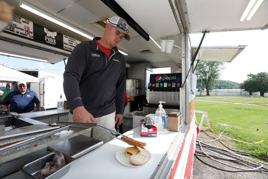 Tanner Kilpatrick serves up a pork tenderloin sandwich at the Muskingum County Fairgrounds on Friday during the Blue Ribbon Food Fair Food Carryout. The event continues each weekend through the end of the month.