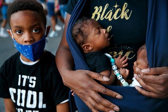Xavier Simmorins, 8, of Baltimore, stands next to his brothers, 8-week-old twins Zuri and Zakai Simmorins, as they are held by their mother Samara Simmorins, during a protest June 7, 2020, near the White House .