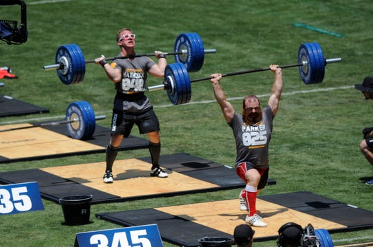 Competitors Lucas Parker (right) and Matt Hathcock (left) participate in the men's clean and jerk during the the CrossFit Games at the StubHub Center in 2013.