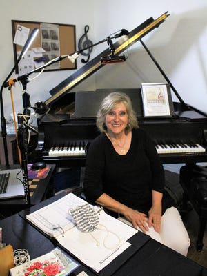 Sherry Frush, at her piano at home. She took lessons at 5 and taught her first student as a fourth-grader. On a table is her music-inspired COVID-19 face mask.