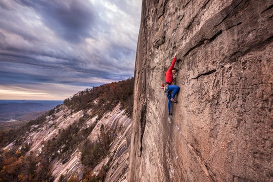 A climber scales a rock face at Table Rock State Park in South Carolina. The Pumpkintown cliffs can be seen in the background, where Carolina Climbing Conservation Corp members are working to build new trail.