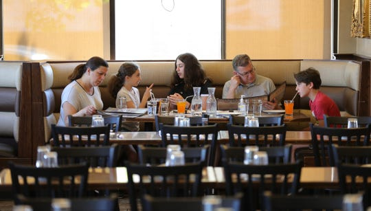 Nadia Abdul-Nour her kids lea, Angela, husband Khaled Abdul-Nour and Marc dine at Al-Ameer Monday, June 8, 2020 in Dearborn Michigan. The restaurant owners have removed tables to meet the six foot requirement, they sanitize menus after each use and all staff wears a mask.Nadis