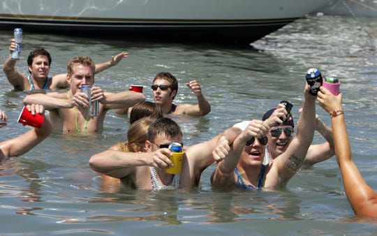 Partygoers wade their way through the water drinking beer during Jobbie Nooner on Lake St. Clair off Harsens Island, Mich., in 2010.