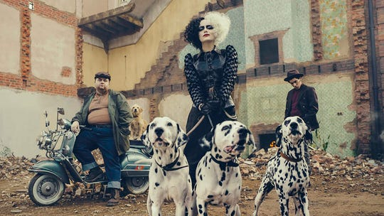 "Paul Walter Hauser, Emma Stone and Joel Fry in ""Cruella."""