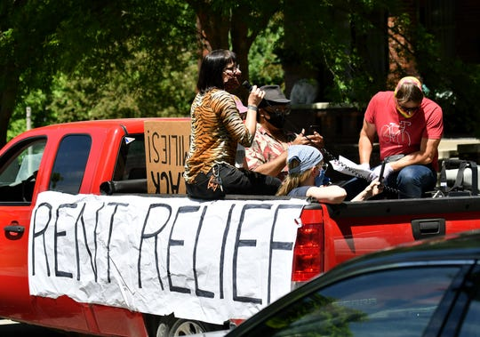 Tenant Jo Messer, 31, of Detroit, with microphone, Detroit Eviction Defense and other groups participate in a caravan protest on Detroit's east side on Tuesday.