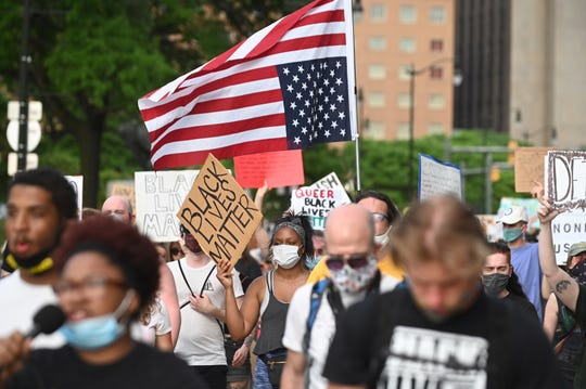 An American flag is turned upside down as protesters march along Michigan Avenue on Tuesday, June 9, 2020.