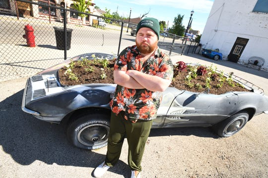 Actor Paul Walter Hauser in front of a Corvette flower garden in front of Dynamic Corvettes in hometown Saginaw, Michigan on June 9, 2020.