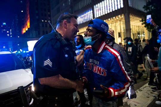 A police officer and protester shake hands during the second straight day of demonstrations against the alleged killing of George Floyd by Minneapolis police in Detroit on Saturday, May 30, 2020.
