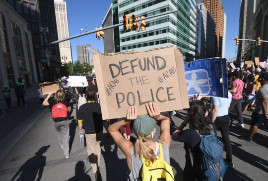 A protester holds a sign to defund the police during a march in downtown Detroit.