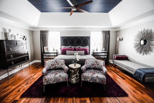 """A cherry blossom fabric on the chairs at the end of the bed in Jerry and Lisa Zimmer's master bedroom ties in Lisa's favorite color, purple. The grasscloth wallpaper in the tray ceiling, meanwhile, ties in Jerry's -- navy. """"We like color,"""" says Lisa. The floor are a Brazilian cherry."""
