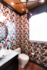 The first floor powder room zings with a bold geometric wallpaper from the Detroit Wallpaper company.  The design is custom made to feature colors already in the Zimmers' house.
