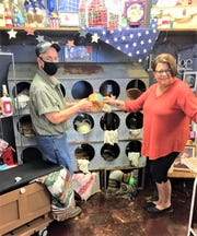 Village Creations owner Diane Reif and crafter Paul Bodi add a basket to the repurposed chicken coop nesting box.