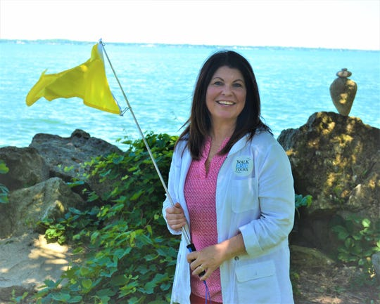 Stacy Maple holds a tour guide flag by the lake shore. Stacy and her husband, Criss Maple, recently opened Walk Erie Tours to highlight the mainland's rich history.
