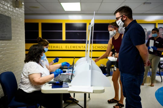 Andy and Erin Sherwood check in before casting their ballots at Whitehall Elementary on primary elections day Tuesday, June 9, 2020.