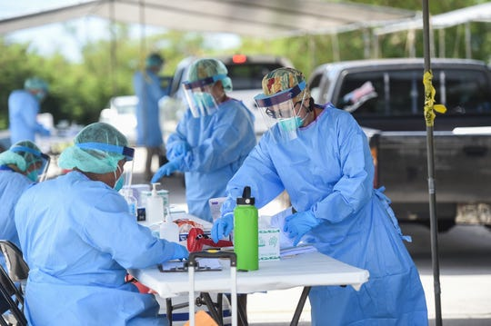 Guam Public Health nurses work at a COVID-19 testing site on the Southern Region Community Health Center parking lot in Inarajan.