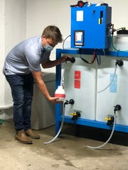 Hometown Roots owner Casey Todd, a partner in the new Pure Spaces disinfection service here, draws a spray bottle of PureSan, a chlorine-based disinfectant, from a water electrolyzing machine. The machine has been installed in the basement of the restaurant to produce both PureSan and a sister disinfectant, PureClean.