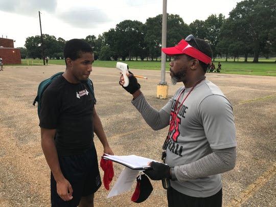 Northside High's assistant football coach Ernest Lazard checks the temperature of Vikings senior Jared-Allen Aaron prior to the start of workouts on Tuesday.