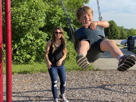 Alli Pacocha helps Landon Hockers swing at the Manchester Hill Park playground. Pacocha has asked Muskego officials to fund a new playground in honor of Landon's twin siblings, who were stillborn.
