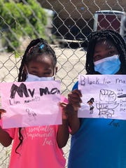 SaMyrah Watts and Lakiesha Taylor hold up homemade signs at a protest in Milwaukee on June 6.