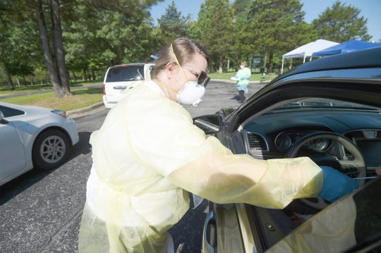 Caitlin Carter, a registered nurse with Boston Mountain Rural Health Center, performs a COVID-19 test on a Mountain Home resident Tuesday during a drive thru testing event at Arkansas State University Mountain Home.