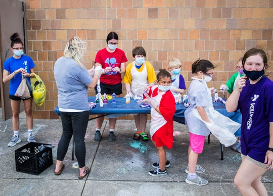 Attendees make tie dye shirts during Day Camp 2020 outside of the downtown Muncie YMCA Tuesday, June 9, 2020.