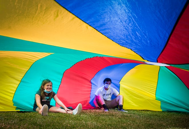 Children play games during Day Camp 2020 with a parachute outside of the downtown Muncie YMCA Tuesday, June 9, 2020.