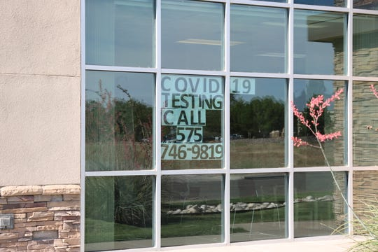 A sign in the window at the Eddy County Public Health Office in Artesia reminds people to call and get tested for COVID-19.