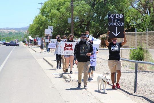 Members of the state public defender's office in Aztec and the community march along Aztec Boulevard on June 8 as part of a protest organized by Public Defenders for Racial Justice.