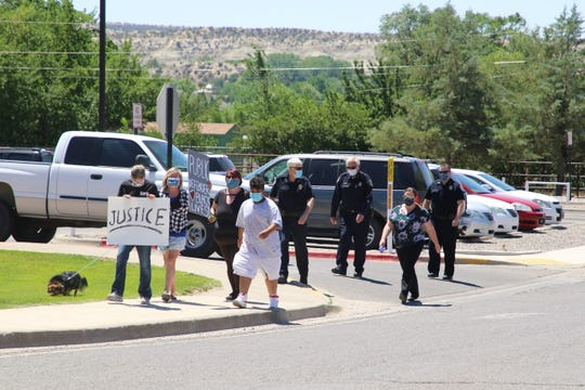 Farmington Police Chief Steve Hebbe, center, walks with the community and department members along South Oliver Drive in Aztec as members of the state public defender's office in Aztec and the community marched on June 8 as part of a protest organized by Public Defenders for Racial Justice