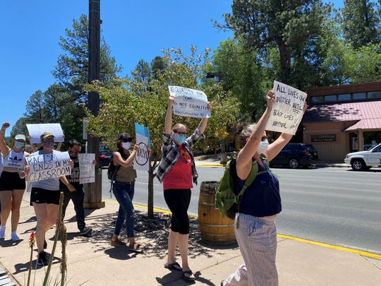 Protesters in Ruidoso held their signs high during the Walk for Solidarity march on June 8.
