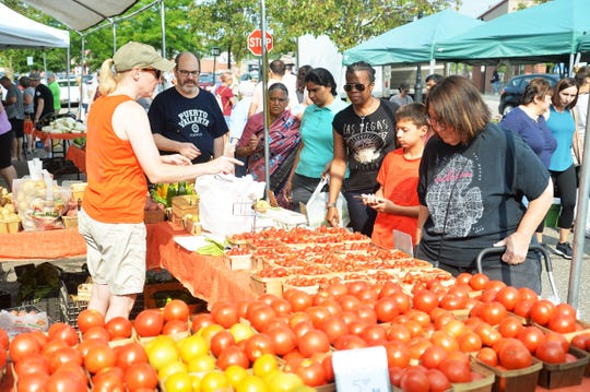 Shoppers eye the tomatoes at an August 2018 market day.