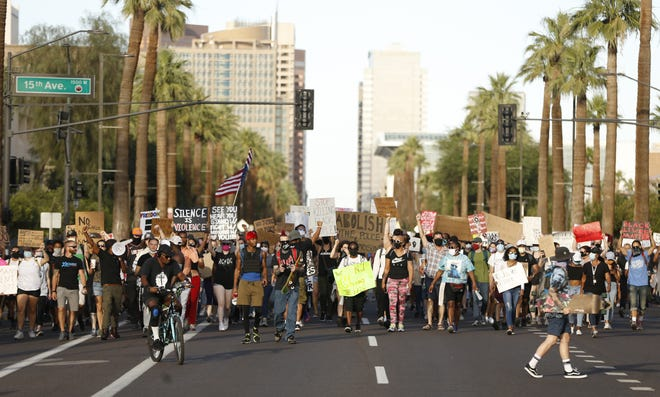 Protesters make their way down Washington Street toward the state Capitol as they march against police brutality in Phoenix on June 8, 2020.