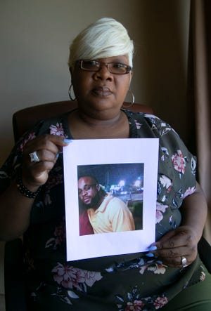Tonya Davis, holds a photograph of her brother, Muhammad Muhaymin, at her attorney's office in Scottsdale on June 9, 2020.