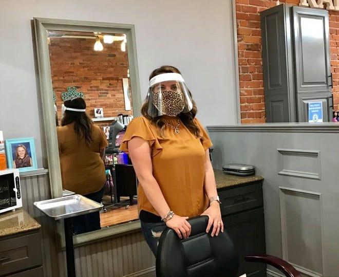 Shannon Karas, owner of Karas & Co. in downtown Port Huron, poses for a photo with a face guard and mask. Salon employees will be wearing masks when the salon opens June 15 and will wear the face guards upon customer request.