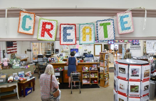 Shoppers practice social distancing while checking out Tuesday, June 9, 2020, at Gruber's Quilt Shop in St. Cloud.
