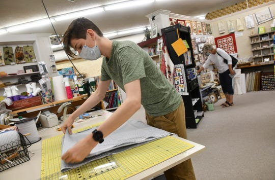 Peter Doroff helps a customer Tuesday, June 9, 2020, at Gruber's Quilt Shop in St. Cloud.