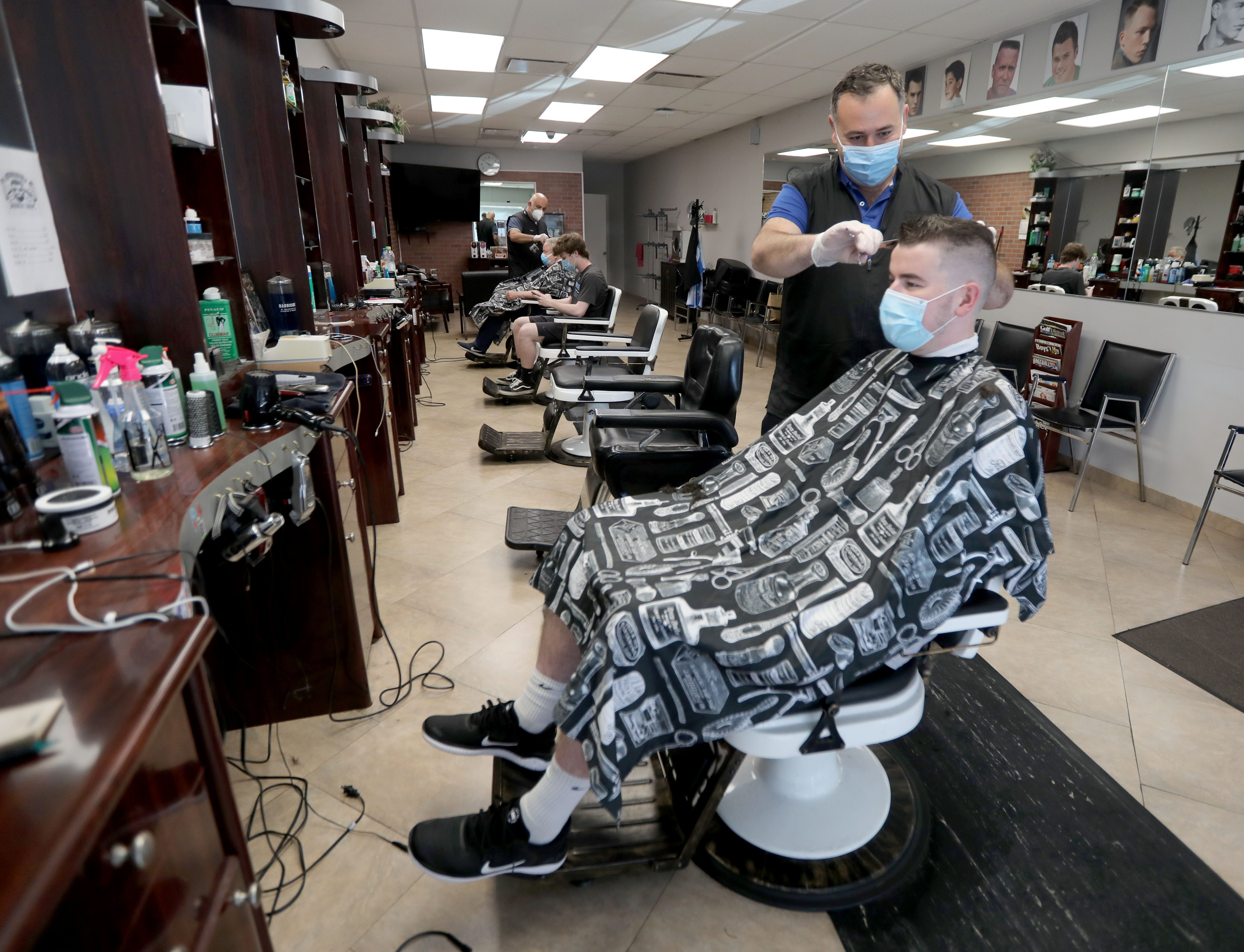 As part of a four-phase economic reopening plan, Gov. Andrew Cuomo gave the green light to launch Phase 2 in parts of the state in June, opening retail stores, hair salons and barber shops like Alex Gavrielov's, seen here cutting 21-year-old Sean Crowley's hair days after reopening in Briarcliff Manor in June.