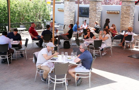 People enjoy lunch under umbrellas at Lilly's on Mamaroneck Avenue in White Plains June 9, 2020. Tuesday was the first day restaurants could open up with outside dinning.