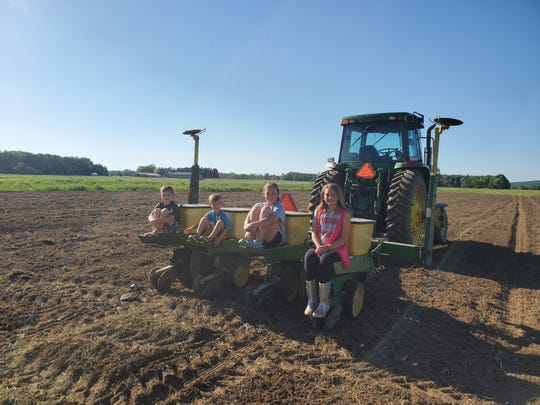 From left to right: Jacob Marti, 8, Ryan Marti 5, Allison Marti, 12, and Chloe Marti, 8, sit on their corn planter.