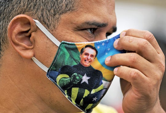 A supporter of President Jair Bolsonaro wears a face mask with Bolsonaro's image during a demonstration at Copacabana beach in Rio de Janeiro, Brazil, on June 7, 2020.