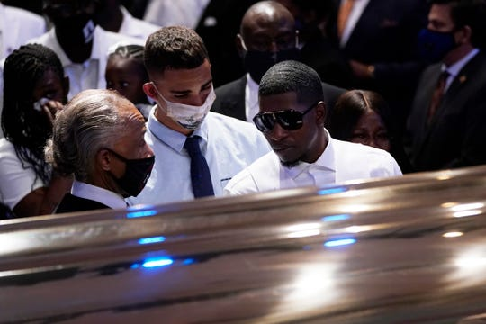 Quincy Mason Floyd, son, of George Floyd pauses at the casket and speake with the Rev. Al Sharpton, left, during a funeral service for Floyd at The Fountain of Praise church, June 9, 2020, in Houston.