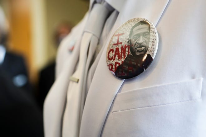 """""""I can't breathe"""" button on the lapel of a mourner at George Floyd's funeral"""